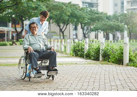 Young Asian nurse taking senior man in wheelchair to the park