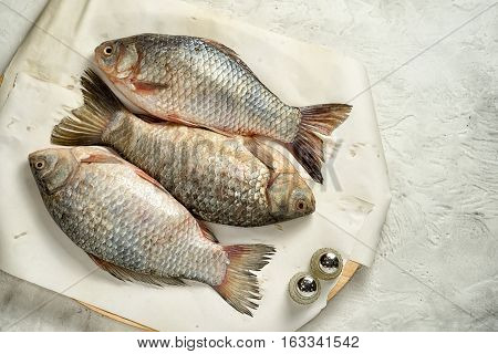 Three fresh carp on a cutting board with paper salt and pepper mills top view. Copy space for your menu inscription.