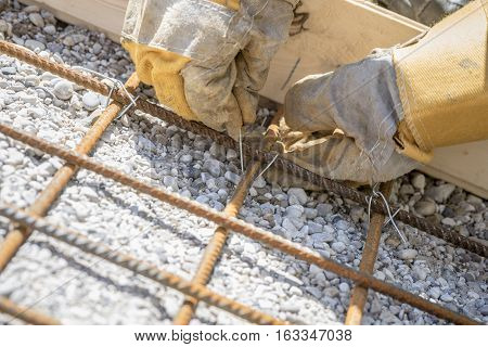 Construction worker tying steel reinforcing rods with string to position them over a stone gravel base close up of the gloved hands.