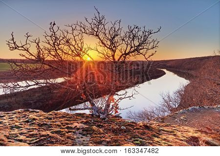 A view of a sunset on the Osage River In Monegaw Springs Missouri with a tree in the foreground.