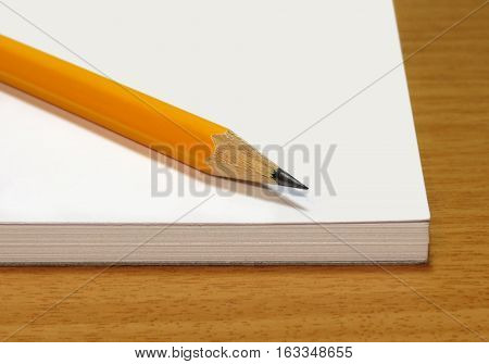 Note pad with a yellow pencil on a wooden table