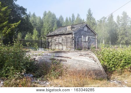 Old Wooden warehouse, barns, sheds on the shore. Misty morning by the sea. Wooden boat this side.
