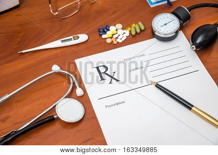 rx prescription with pills stethoscope thermometer and pen