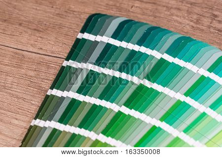 Green colour sample chart close up on desk