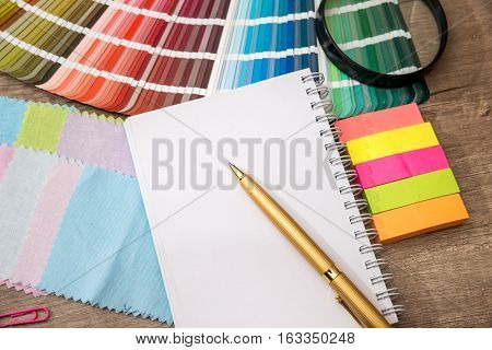 Colour swatches book with notepad and pen