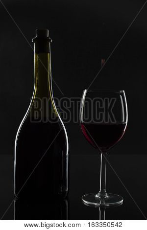 The bottle of wine and a drop in the glass, on the dark background and in a technique low-key.