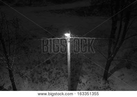 black and white photograph of a street lamp in the snow
