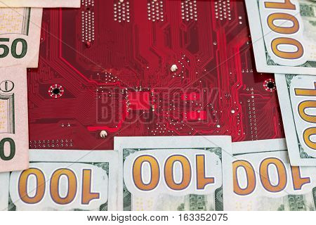 Closeup of one hundred dollar with red computer motherboard