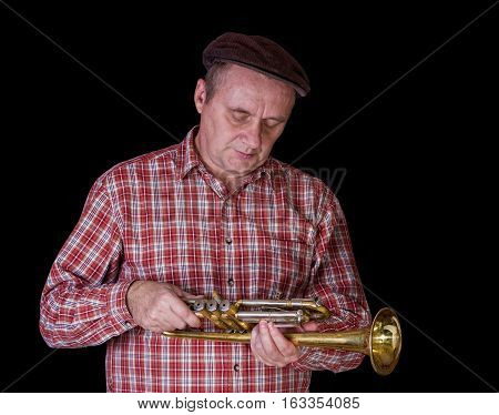 Portrait of mature tuner examining the instrument - trumpet.