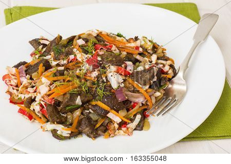 Warm salad with crab sticks and mushrooms in white plate. Studio Photo