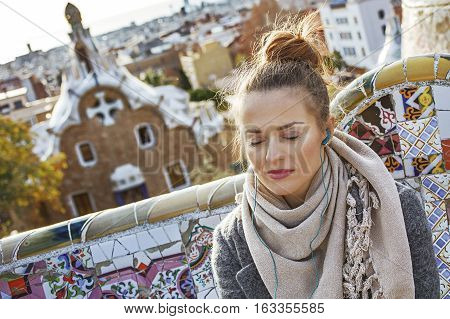 Woman Listening Audioguide While Sitting On Bench In Barcelona