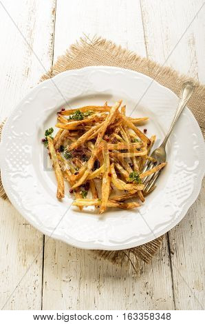 french fries with salt red peppercorn parsley and fork on a white plate