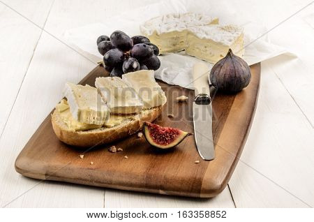 half bread roll with camembert on a wooden board also with a fig and red grapes