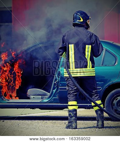 Firefighter During Shutdown Of A Fire Of A Car