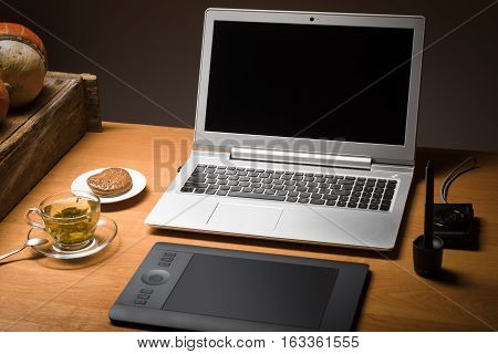 Desktop of a photographer with laptop graphical pen tablet compact camera and green tea