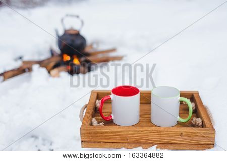 Romantic winter picnic. Two cups on a wooden tray in snow. Copper kettle over an open fire on background blurred. Boiling kettle on firewood. Copy space. Lifestyle camping.