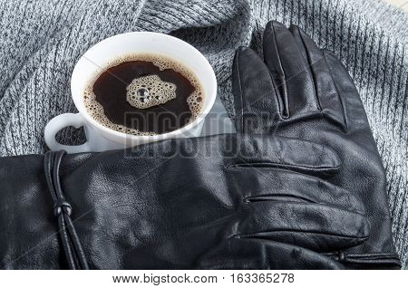 View Close-up On Black Women's Gloves And A White Coffee Cup
