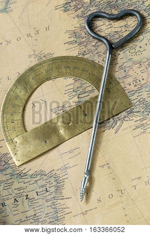 old protractor and hand drill gimlet on vintage map, macro background, compasses, Atlantic ocean