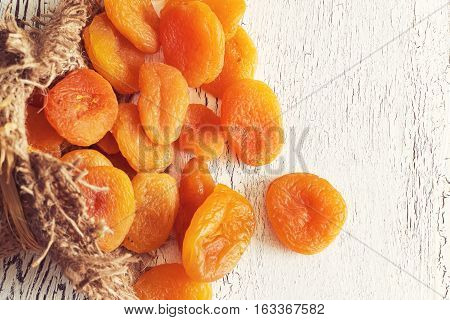 Dried apricots on white rustic wooden background. Top view with copy space