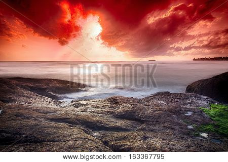 Infernal sunset in the ocean - wide angle landscape photo of ocean waves with long exposure.