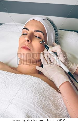 Close up of young pretty woman getting rf lifting treatment on clinical center. Medicine, healthcare and beauty concept.