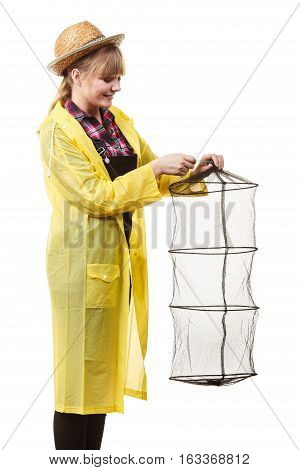 Spinning angling cheerful fisherwoman concept. Happy woman in yellow raincoat holding empty fishing keepnet having fun.