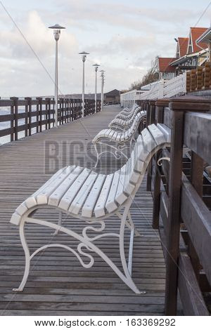 View across and empty deserted row of benches at the end of the pier looking towards the promenade.