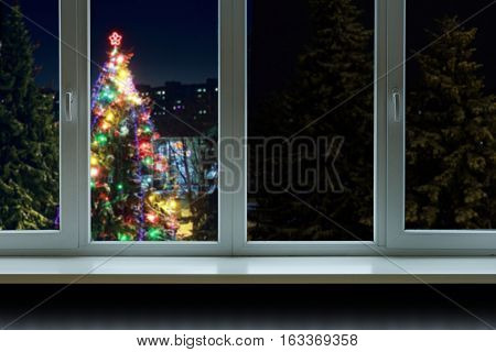 A large decorated Christmas tree outside the window