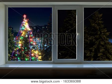 Christmas tree with Christmas lights outside the large window