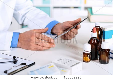 Doctor's Hands Working On A Digital Tablet At His Office