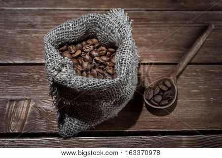 Coffee beans in a hessian sack and scoop on a brown wooden background