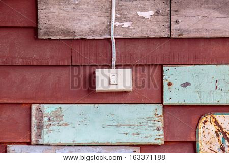 Electric lighting switch with old wooden plank on the background.