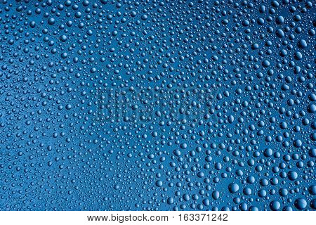 misted glass with drops water close up on a blue background