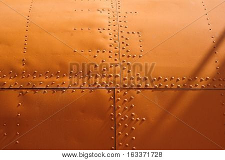 orange texture covering aircraft rivets for background.