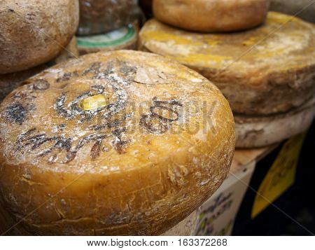 Cheese wheels of fontina. On sale in a food street market.