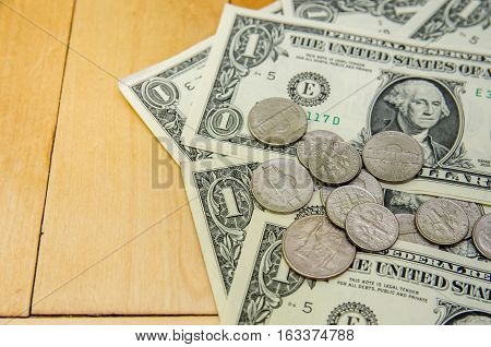 american one dollars and coins above parquet
