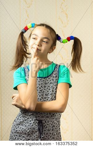 Portrait Of A 11 Year Old Girl With Funny Tails In Her Hair, Put His Finger To His Lips And Think Wi