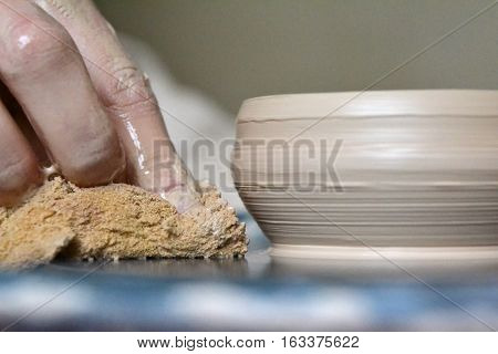 The potter makes earthen vessel close. Stained hands in the clay and the clay plate