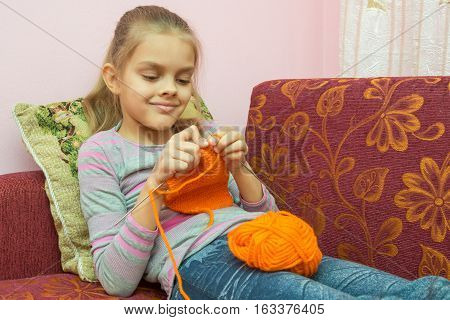 Girl Lying On The Couch And Knits On Spokes