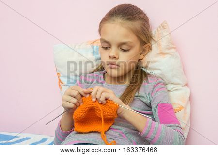 The Girl Knits On Spokes Sitting On The Bed