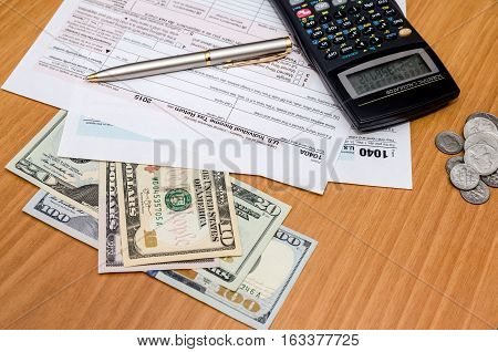 1040 tax form with us coin and dollar calculator pen