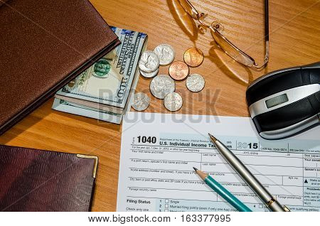 1040 tax form for 2016 with pen money notepad calculator