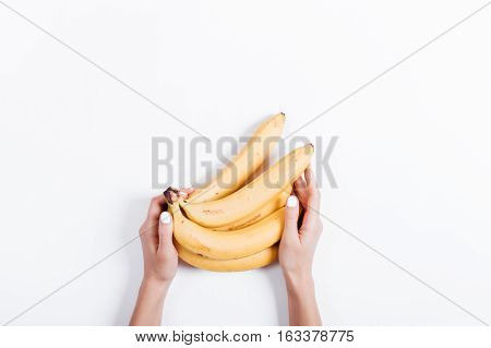 Female hand holding a bunch of bananas on a white table top view