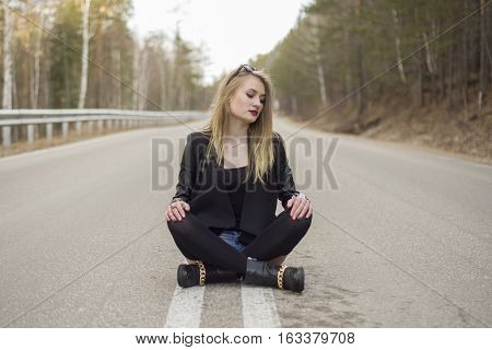 Beautiful Young Girl Sitting In The Middle Of The Road.