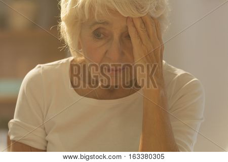 Photo of worried ill senior woman having headache