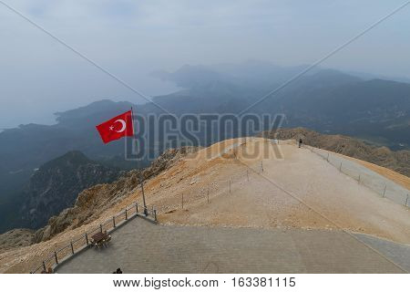 Turkish Flag at the Top of the Tahtai Dagi - Olympos Mountain in Kemer with Olympos Beach in the Background and the Mediteranian Sea
