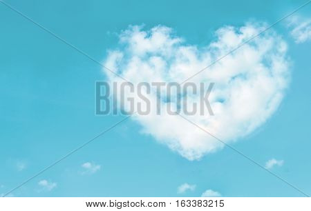 Beautiful clouds in heart shape on blue sky. Love nature concept. Vintage style.