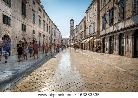 Shiny street of marble, Dubrovnik. Dubrovnik, Croatia - July 18, 2015: Shiny street made of marble in Dubrovnik with people passing by. Perspective view.  People on street in Dubrovnik.