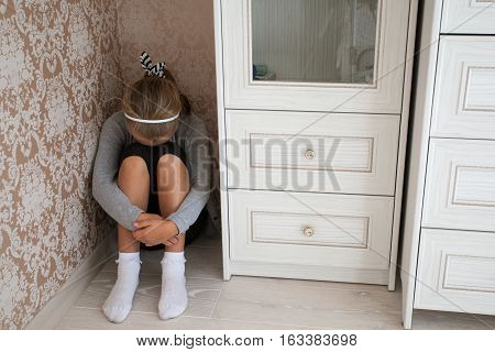 Sad little girl sitting in the corner of a room head is lowered, legs are clasped by the hands