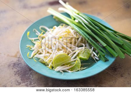 Close up of bean Sprouts and lemon eating with Pad Thai on green dish